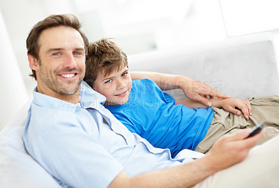 Buy stock photo Portrait of a happy young man and his son sitting together on couch watching television at home - Indoor