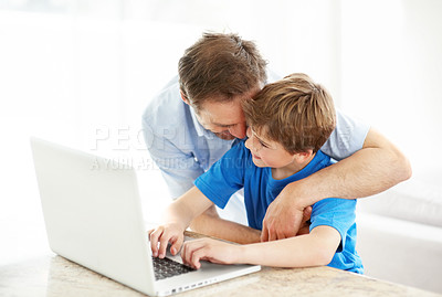Buy stock photo Portrait of a happy young father hugging his son working on laptop - Indoor