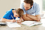 Smiling young man helphing his son with schoolwork