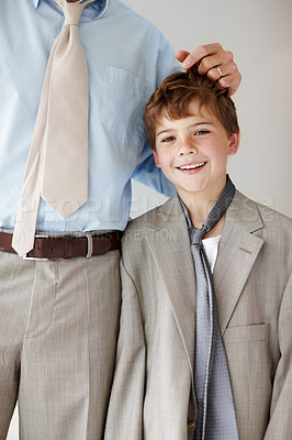 Buy stock photo Portrait of a happy little boy wearing an oversized coat standing with his father