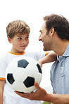 Young boy looking at his father holding a football