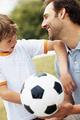 Buy stock photo Portrait of a cute little boy looking at his smiling father holding football