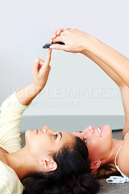 Buy stock photo Portrait of young friends holding cellphone while lying together on the floor