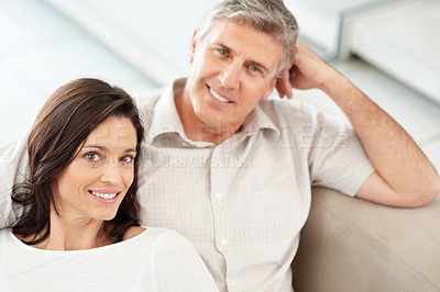 Buy stock photo Portrait of a happy middle aged couple smiling while sitting together on sofa at home