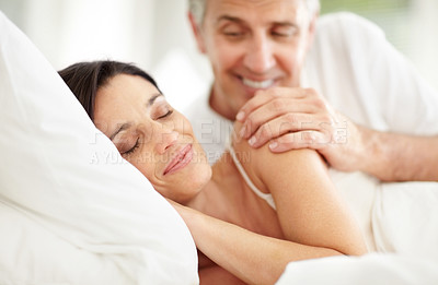 Buy stock photo Portrait of smiling mature man looking at his wife sleeping on bed
