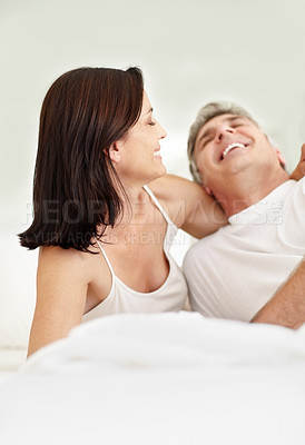 Buy stock photo Portrait of happy mature couple smiling together and lying in bed