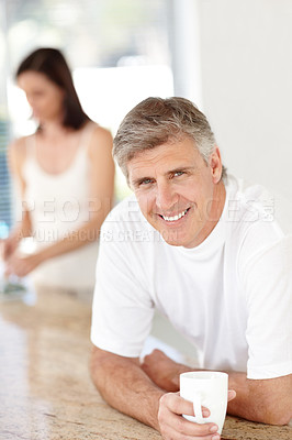 Buy stock photo Portrait of mature man drinking coffee with his wife standing in background