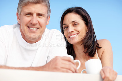 Buy stock photo Portrait of happy mature couple having coffee together and looking at you against sky