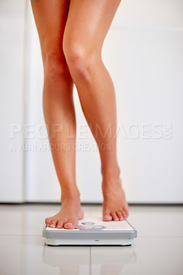 Buy stock photo Beautiful legs of a young woman measuring her weight on a bathroom scale
