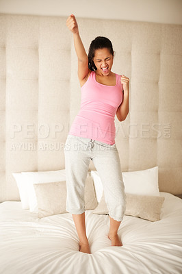 Buy stock photo Portrait of an excited young woman celebrating success while standing on the bed