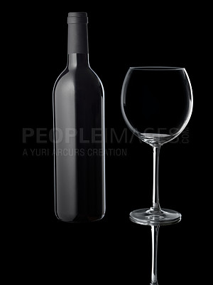 Buy stock photo A wineglass with a dark bottle in the background
