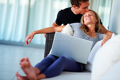 Buy stock photo Portrait of a handsome young boy kissing her girlfriend while working on laptop