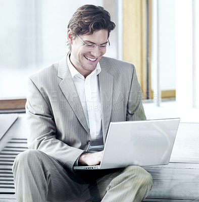 Buy stock photo Young cheerful businessman working on laptop in an urban setting