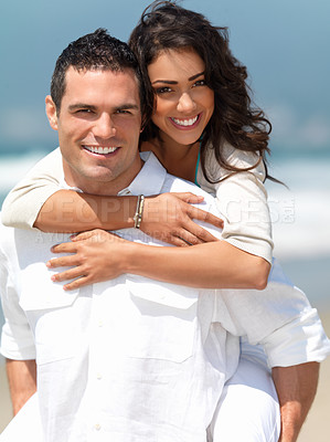 Buy stock photo Portrait of a happy young couple having fun on the beach. Couple enjoying a summer vacation.