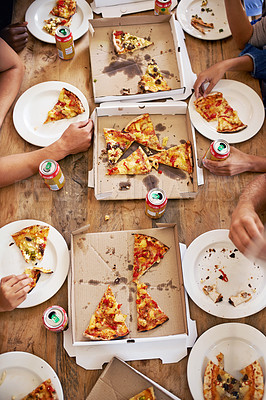 Buy stock photo A cropped high-angle shot of a group of people sharing boxes of pizza at a table