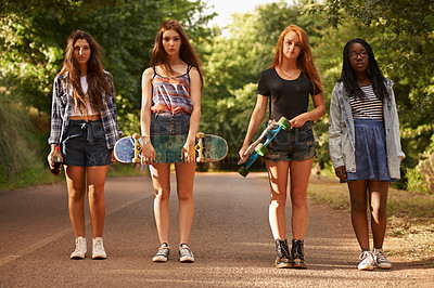 Buy stock photo Full length shot of a group of young girls standing outdoors with their skateboards