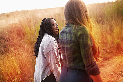 Buy stock photo Two young friends bonding outdoors as they walk through nature