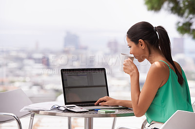 Buy stock photo A young woman working hard while drinking a cup of coffee outdoors