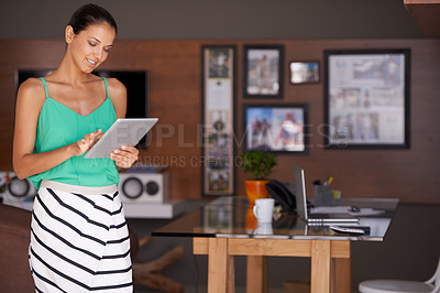 Buy stock photo A young woman standing in her home office using a digital tablet