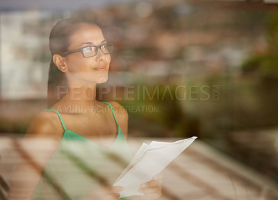 Buy stock photo A cropped shot of a young woman holding a document indoors