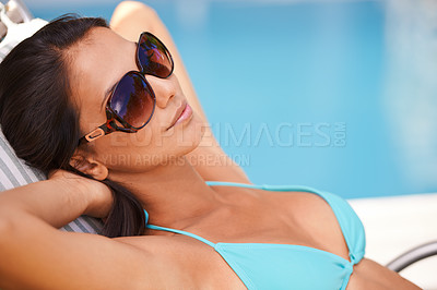 Buy stock photo Shot of a beautiful young woman relaxing in a lounge chair by a swimming pool