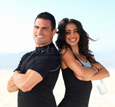 Buy stock photo Portrait of a smiling young fit couple or a pair of personal trainers against sky