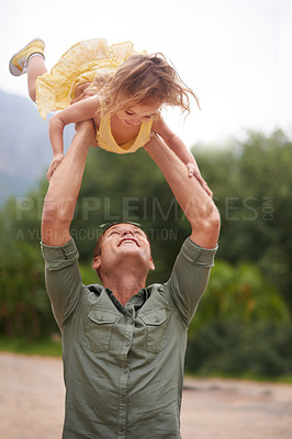 Buy stock photo A father playfully holding his little girl above his head