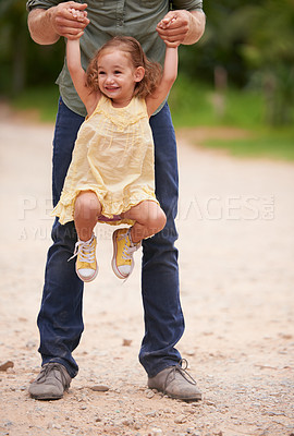 Buy stock photo A little girl being playfully lifted into the air by her dad