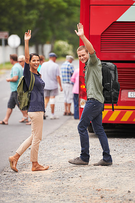 Buy stock photo A happy couple wave farewell as they walk towards their bus