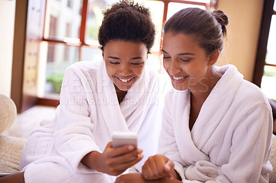 Buy stock photo Shot of two friends in bathrobes using a cellphone at a spa