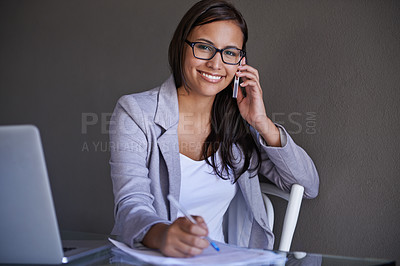Buy stock photo An attractive young businesswoman talking on the phone while working at her desk