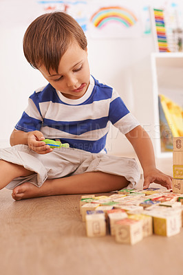 Buy stock photo a young boy playing with his building blocks in his room