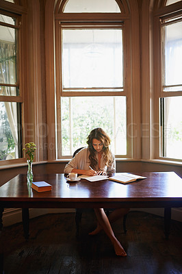 Buy stock photo Shot of an attractive young woman writing in a relaxed environment at home