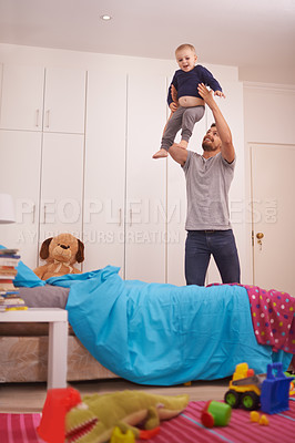 Buy stock photo A young father playing with his young son at home