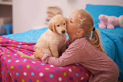 Buy stock photo A cropped shot of a little girl kissing her puppy while it sits on her bed