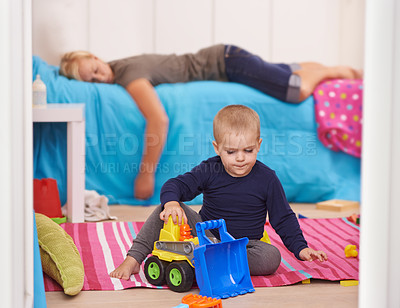 Buy stock photo A toddler playing with his toys while his mom naps on his bed