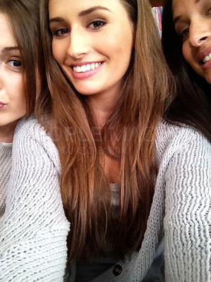 Buy stock photo Cropped shot of three beautiful young women taking a selfie