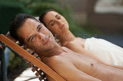 Buy stock photo Cropped shot of a mature couple relaxing side by side on lounge chairs outside