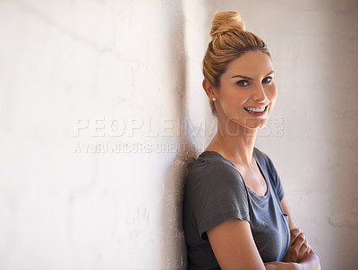 Buy stock photo Portrait of an attractive young woman leaning against a brick wall