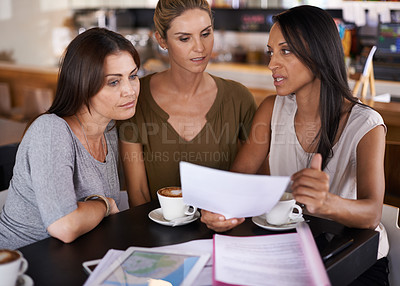 Buy stock photo Three women discussing paperwork during a business meeting at a cafe