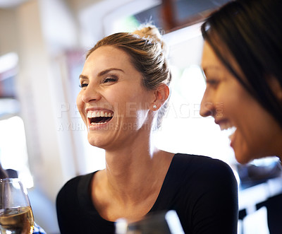 Buy stock photo Cropped shot of two women enjoying a glass of wine at a restaurant