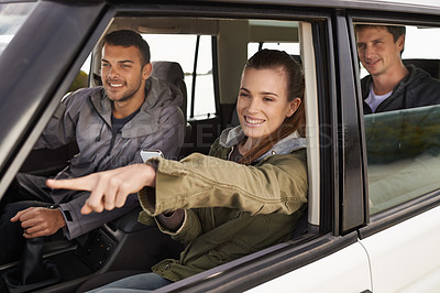 Buy stock photo Shot of a young woman shpowign her friend where to go while on a roadtrip