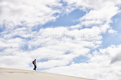 Buy stock photo Shot of a young male hiker walking along the sand dunes