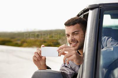 Buy stock photo Shot of a handsome young man taking a photo out the window of his car with his phone