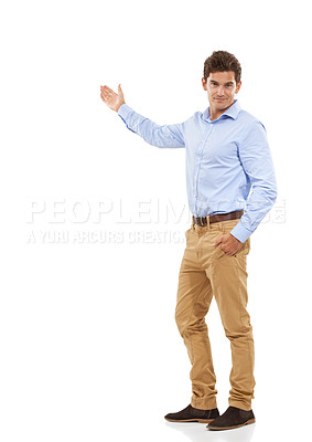 Buy stock photo Portrait of a handsome young man in a studio gesturing to the side with one arm