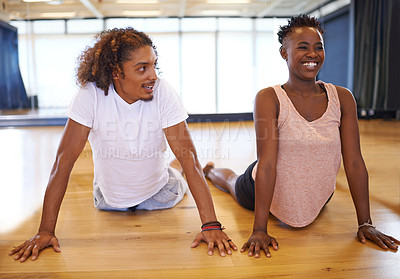 Buy stock photo Shot of two young dancers warming up in a dance studio