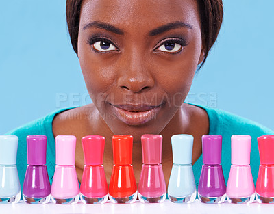Buy stock photo A young african woman looking over a row of colorful nail polish