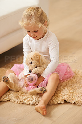 Buy stock photo Shot of a little girl in a tutu playing with a puppy