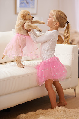 Buy stock photo A little girl dressing her puppy in a tutu