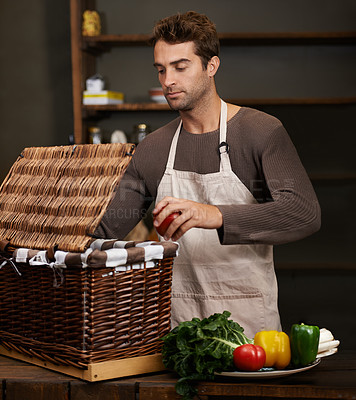 Buy stock photo Shot of a young man packing vegetables into a basket